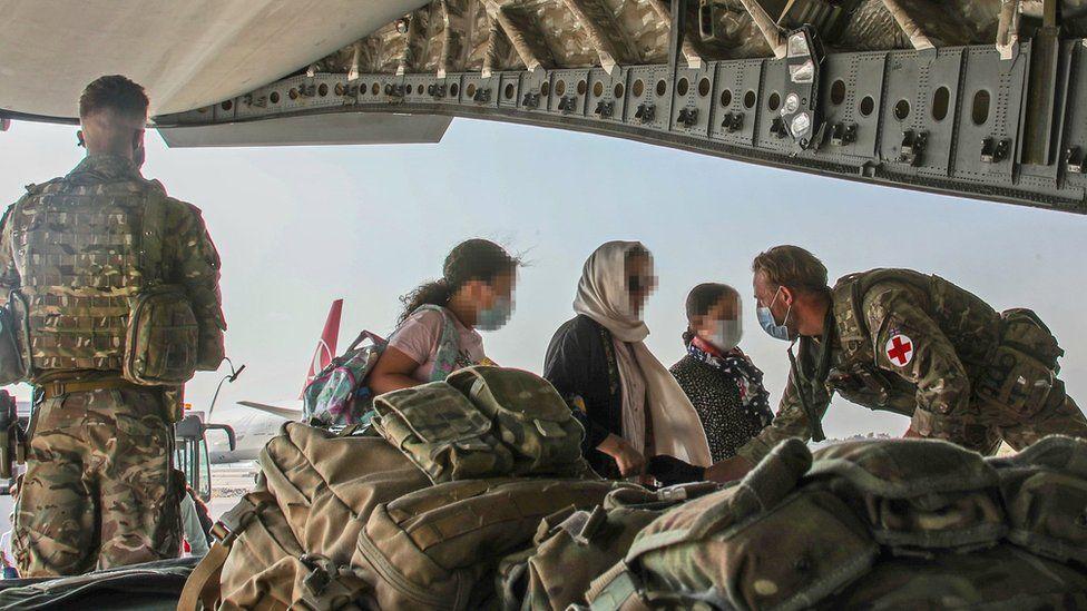 UK troops help Afghan nationals board an RAF plane in Kabul