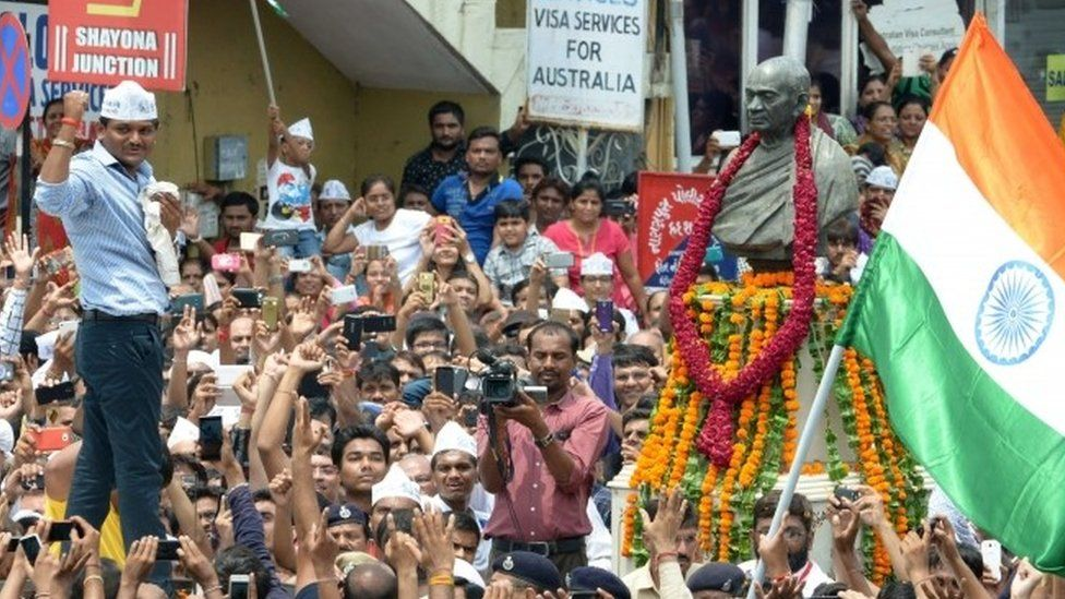 Hardik Patel raises his fist near the statue of Sardar Vallabhbhai Patel