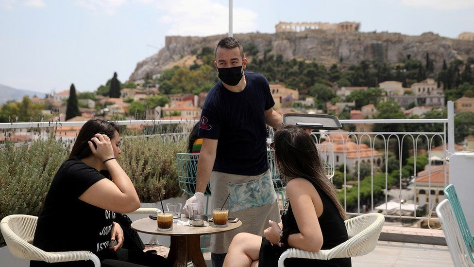 A waiter wearing a protective face mask serves customers in a coffee shop, with the Acropolis hill in the background, as restaurants reopen following the easing of measures against the spread of the coronavirus disease (COVID-19), in Athens, Greece