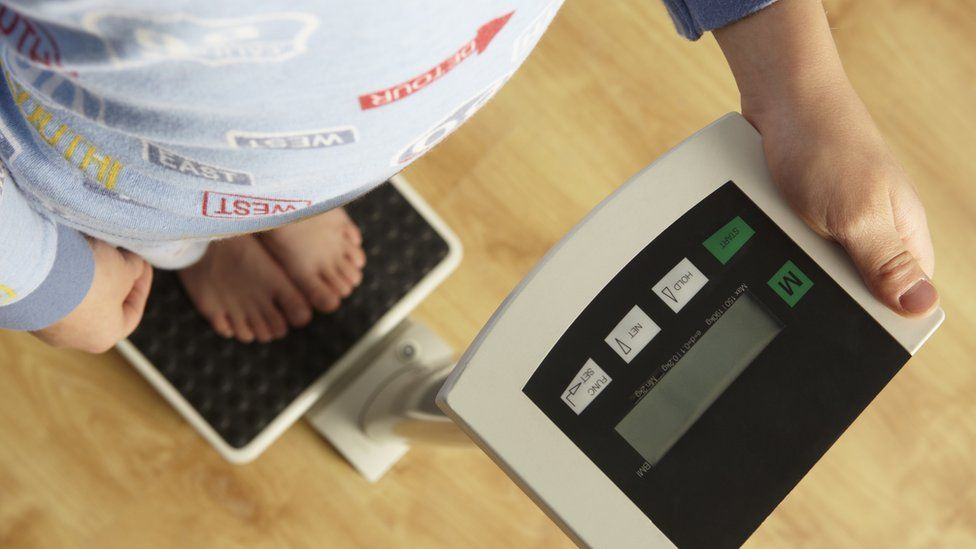 A little boy on a weighing scale