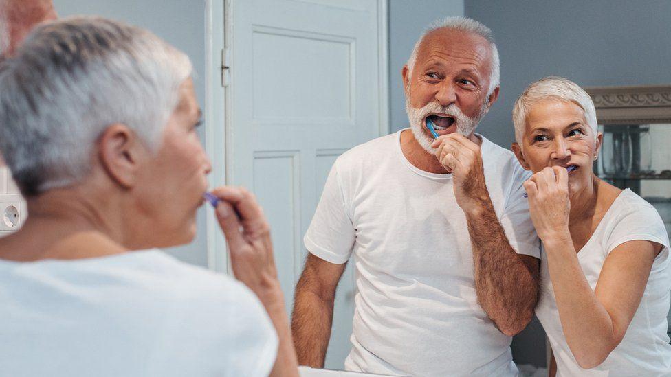 Older people brushing their teeth