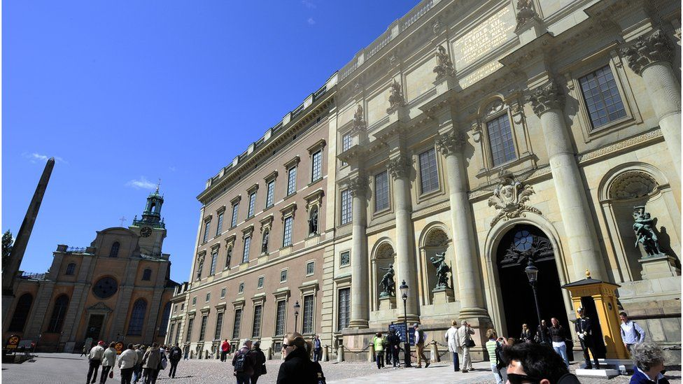 Tourists stroll by the Royal Castle in Stockholm