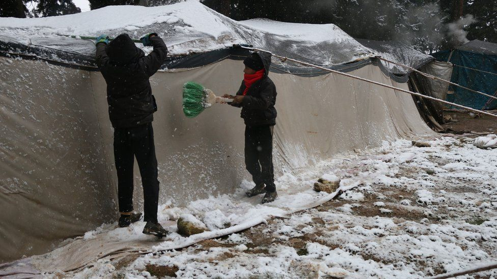 Children clear snow off the roof of a tent a camp for displaced people in Aleppo province, Syria
