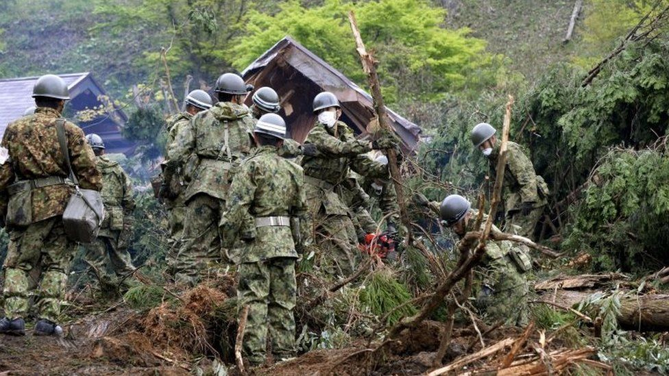 Japan Ground Self-Defense Force soldiers conduct search and rescue operations for a missing guest at a destroyed mountain villa following a landslide site caused by an earthquake in Minamiaso town, Kumamoto prefecture, southern Japan, in this photo taken by Kyodo April 18, 2016.