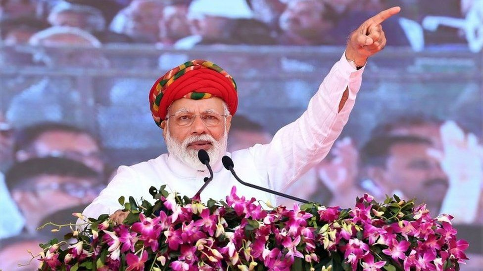 """This handout photograph released by India""""s Press Information Bureau (PIB) on March 4, 2019, shows Indian Prime Minister Narendra Modi addressing a gathering during during the inauguration of various development projects in Jamnagar, in the Indian state of Gujarat. (Photo by Handout /"""