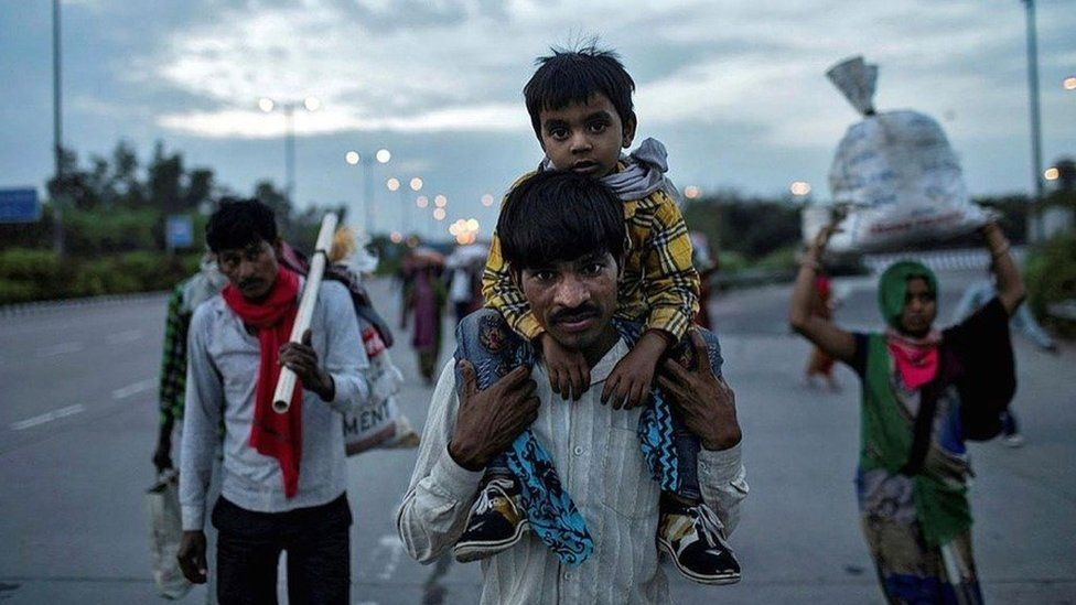 Dayaram Kushwaha carries his 5-year-old son, Shivam, as he and members of his extended family make their way back to his home village from New Delhi.