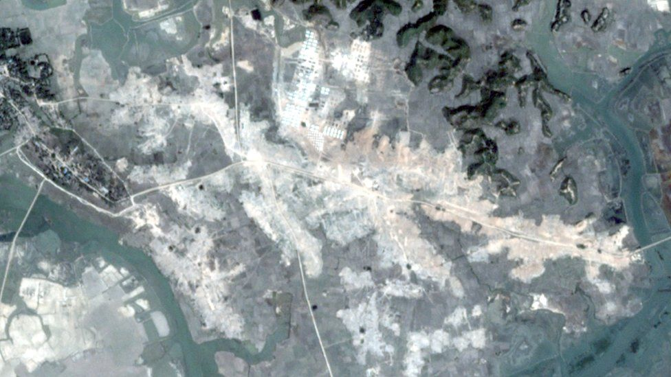 A satellite image shows the layout of a village in bright white - apparently bulldozed ground - in stark contrast to the green landscape around it