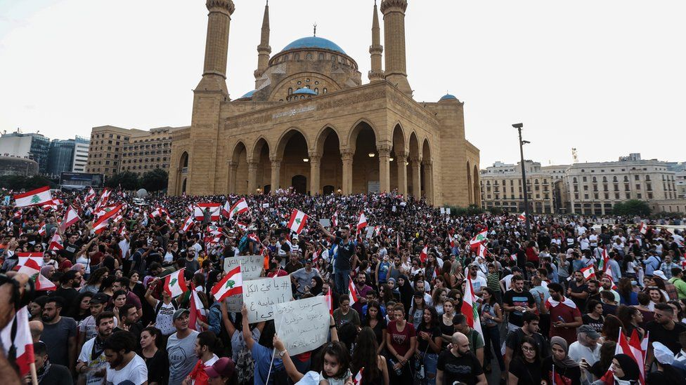 Protesters wave Lebanese flags and shout anti-government slogans in front the government palace in downtown Beirut, Lebanon (19 October 2019)