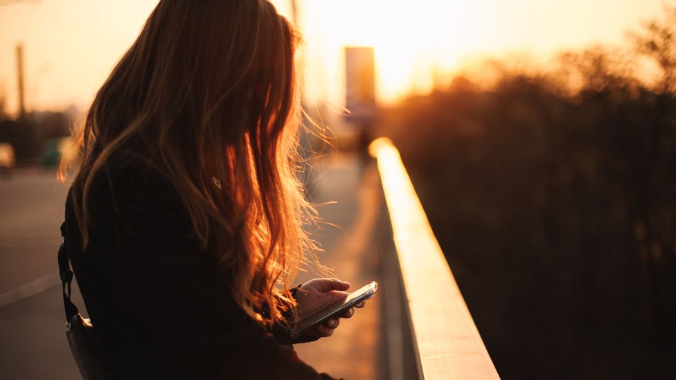 Picture of a young woman looking at her mobile phone
