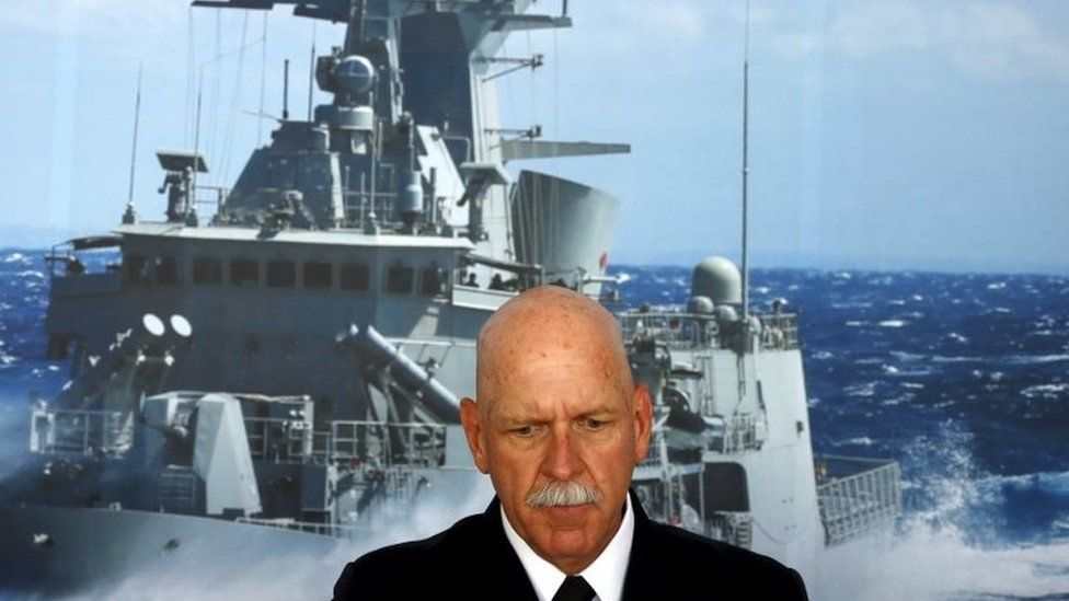 Commander of the US Pacific Fleet Admiral Scott Swift sits in front of a large poster of an Australian Navy frigate in Sydney (15 December 2015)