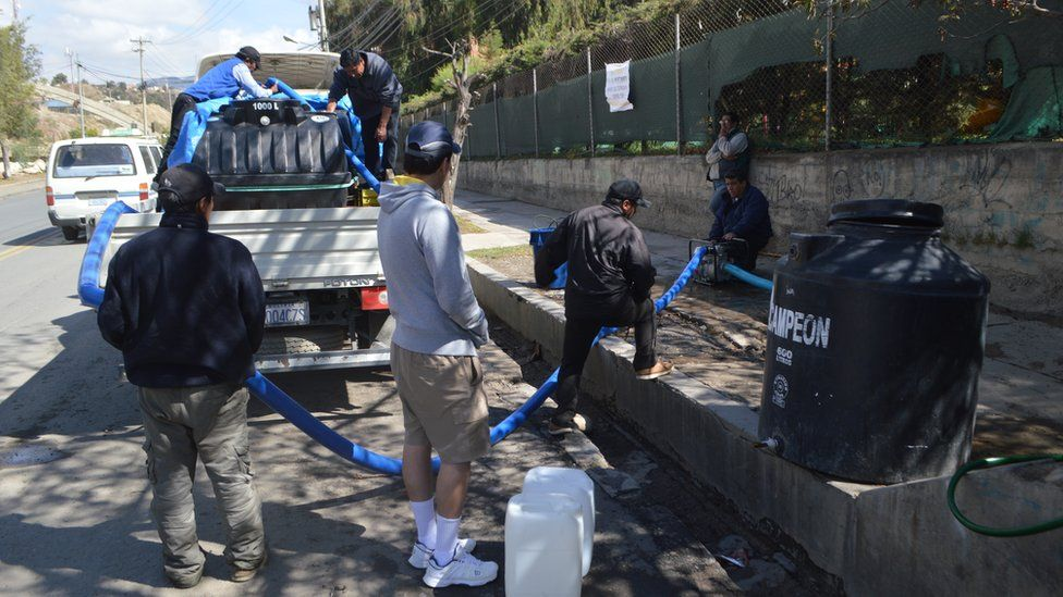 People in La Paz stand next to a lorry delivering water