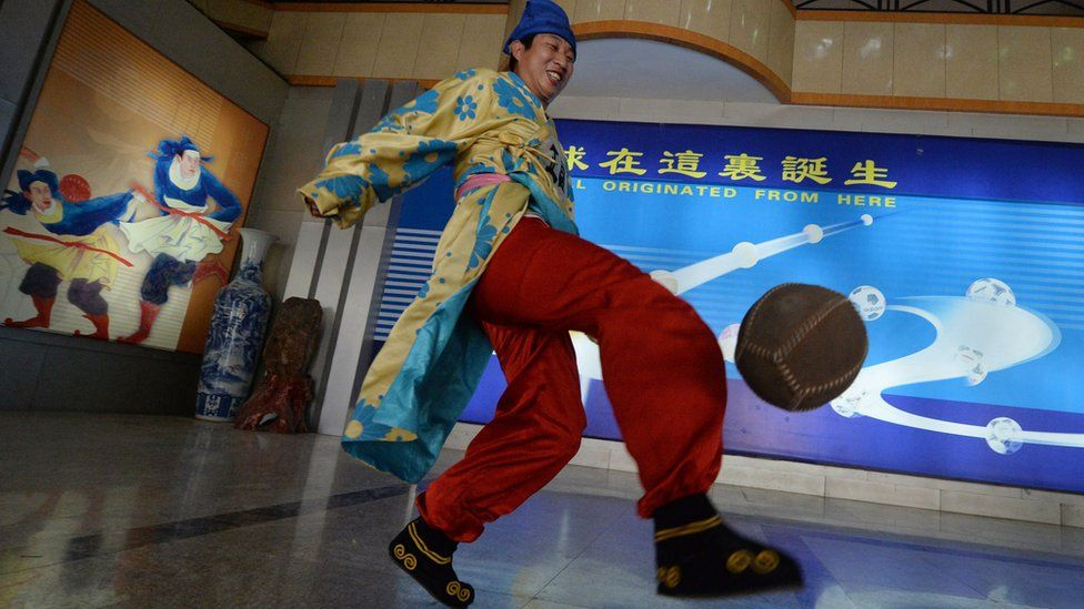 Man in traditional cuju clothes playing with a ball at the Linzi Football Museum in Zibo, Shandong Province