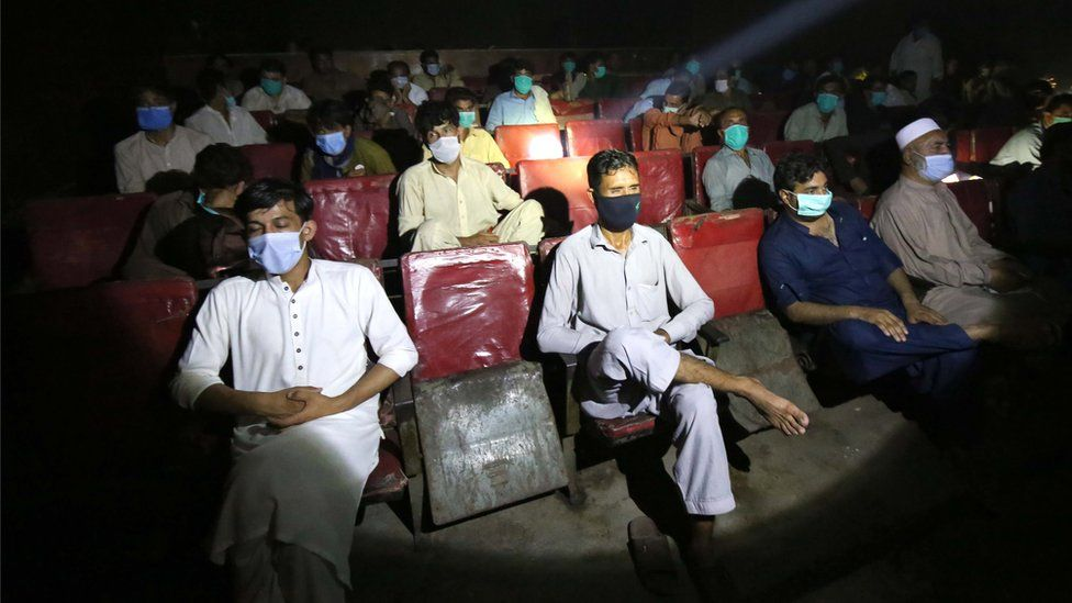People wearing face masks watch a movie in the cinema after the government lifted most of the country's remaining coronavirus restrictions, in Peshawar, Pakistan, 10 August 2020.