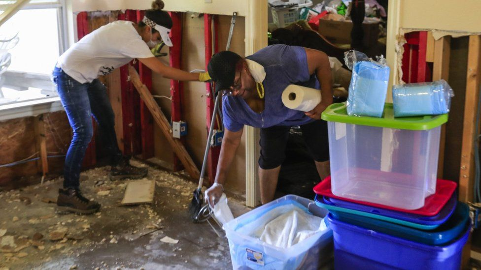 A volunteer works with Barbara Wilson as she begins to clean her house flooded by Hurricane Harvey in the Hunterwoods Village area of Houston, Texas, 3 September 2017