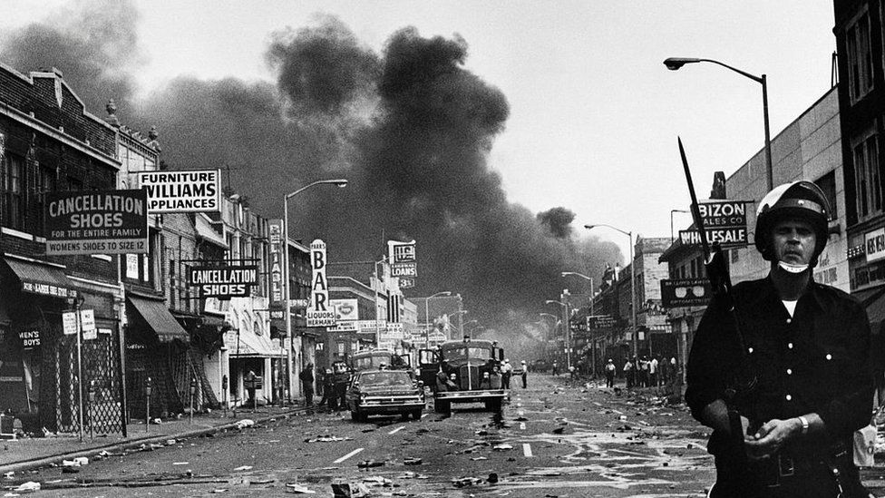 A police officer stands guard in a Detroit street as buildings are burning during civil unrest on 25 July 1967.