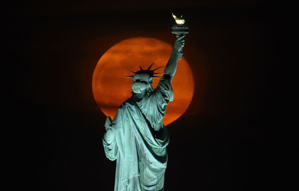 The Pink Supermoon rises above the Statue of Liberty in New York City on 27 April 2021