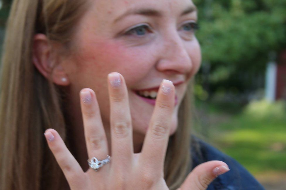 Kristin holding up her hand wearing her engagement ring