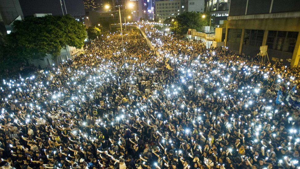 Protestors and student demonstrators hold up their cellphones in a display of solidarity during a protest outside the headquarters of Legislative Council in Hong Kong on September 29, 2014