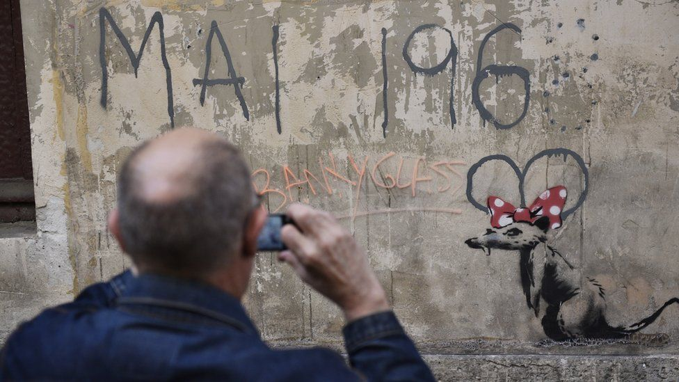 """A man takes photographs of a recent artwork believed to be attributed to Banksy showing a rat wearing a Minnie Mouse bow under """"May 1968"""" in the Sorbonne neighbourhood"""