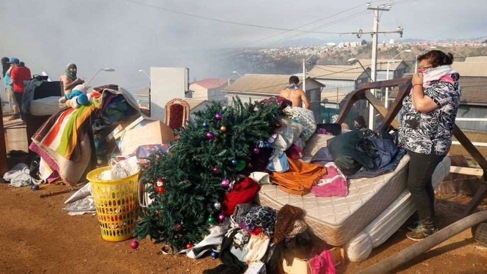 People stand next to their personal belongings in Valparaíso, Chile. Photo: 24 December 2019