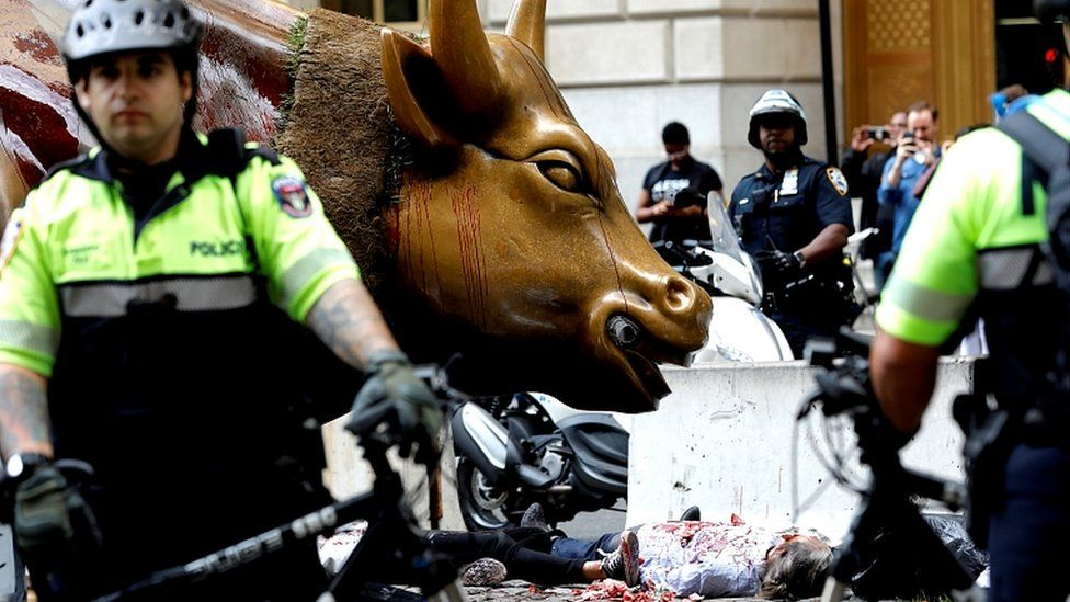 Climate change activists are surrounded by police as they protest at the Wall Street Bull in Lower Manhattan during Extinction Rebellion protests in New York City, October 7, 2019