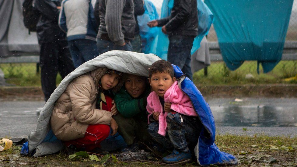 Children take shelter from the rain in Sredisce ob Dravi, a border crossing between Croatia and Slovenia (Oct. 19, 2015)