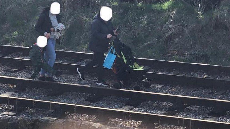 People walking along railway line