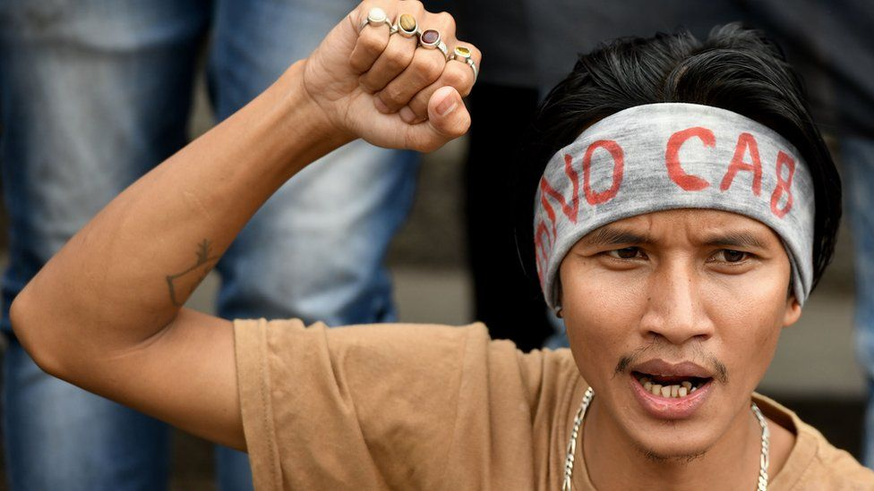 """A protester in Bangalore wearing a headband with """"NO CAB"""" written on it"""