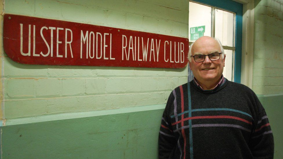 John Gough standing outside Ulster Model Railway Club sign