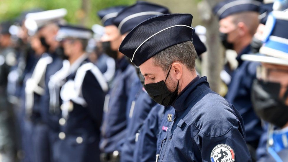 French police officers stand at the ready as they attend a ceremony to pay tribute to police officer Eric Masson, who was killed on May 5 during an anti-drug operation