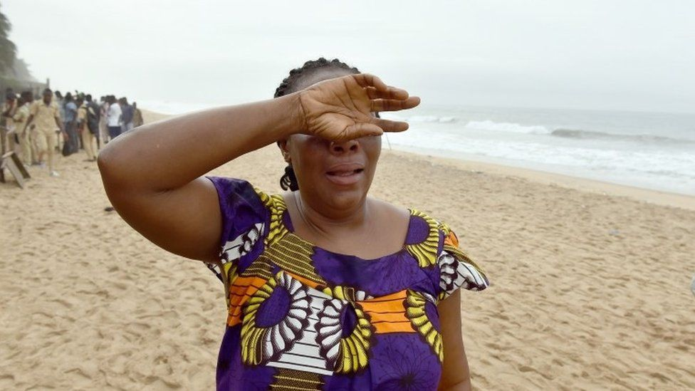 A woman looks for her son along the beach in Grand Bassam, Ivory Coast