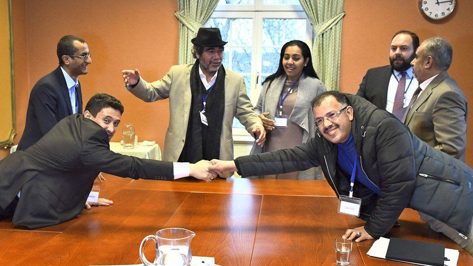 Houthi delegate Abdelqader Mourtada (L) and government delegate Brigadier General Asker Zaeel shake hands at the negotiating table in Stockholm, 13 December