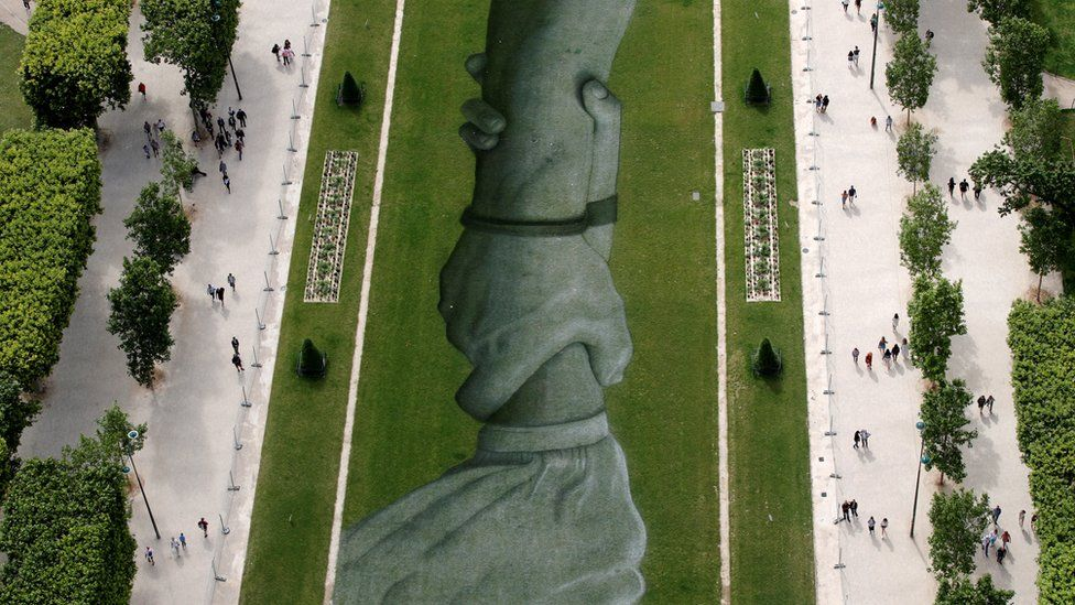 """This aerial picture taken on June 13, 2019 shows a 600 meters long installation by French land artist SAYPE entitled """"Beyong Walls"""""""