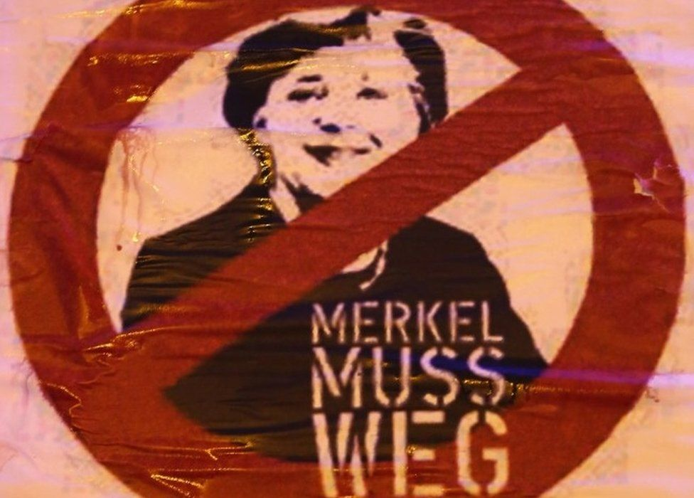 "A sign that reads ""Merkel must go"" hangs froma truck during a rally by supporters of the AfD political party protesting against German Chancellor Angela Merkel""s liberal policy towards taking in migrants and refugees on October 14, 2015"