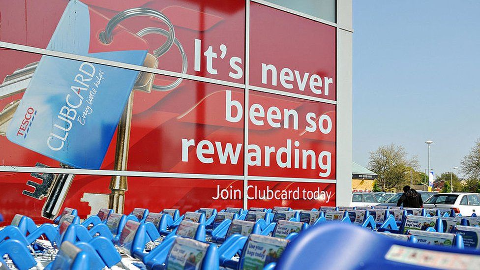 An exterior display of a Tesco shows a huge advert for Tesco Clubcard dominating the building
