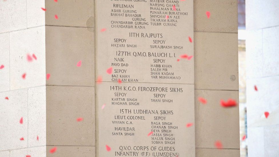 Paper poppies fell to represent the soldiers named on Menin Gate