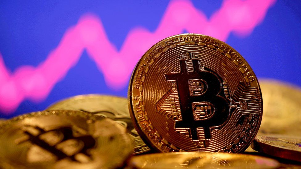 A real-world symbol of a gold Bitcoin on a pile, with a trending upward graph out-of-focus in the background