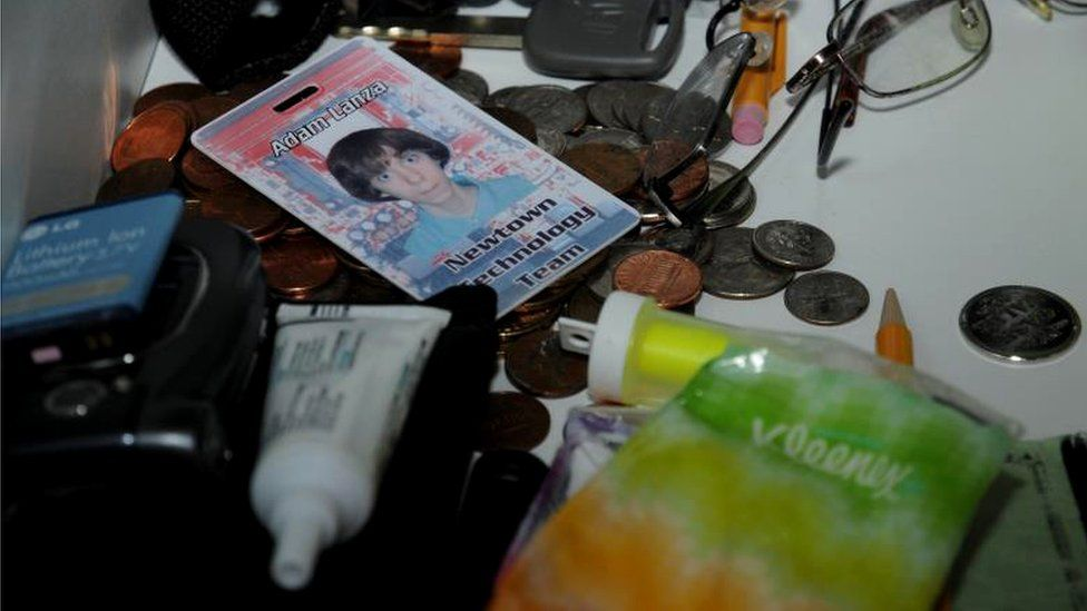 A mess of items contain a technology id card for Adam Lanza