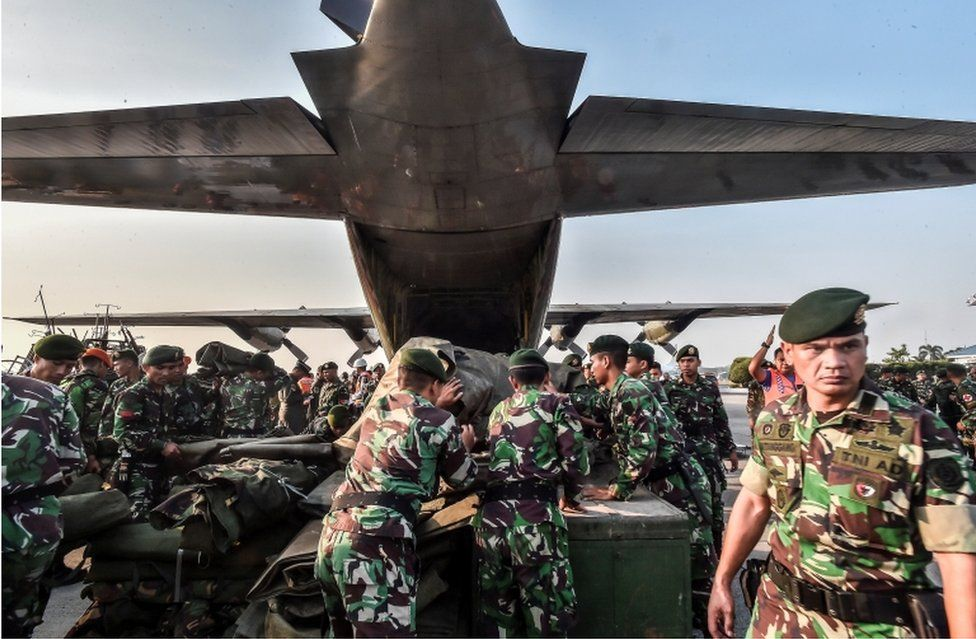 Indonesian soldiers load emergency supplies into a Hercules military plane before heading to Palu
