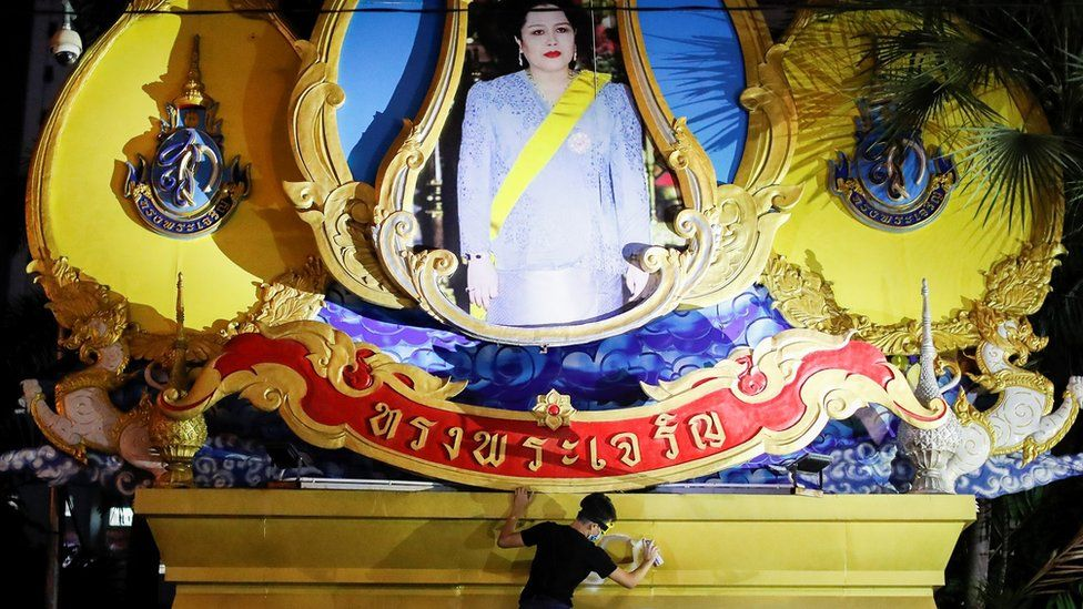 A person spray-paints a pedestal, above which stands a depiction of Queen Mother Sirikit