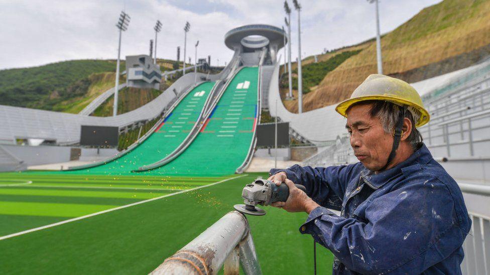 Un trabajador pule la barandilla del centro nacional de saltos de esquí que se está construyendo en el distrito de Chongli para los Juegos Olímpicos de Invierno de Beijing 2022 el 28 de julio de 2021 en Zhangjiakou, provincia de Hebei, China