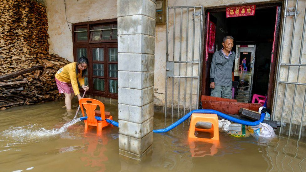 Residents pump flood water out of their house
