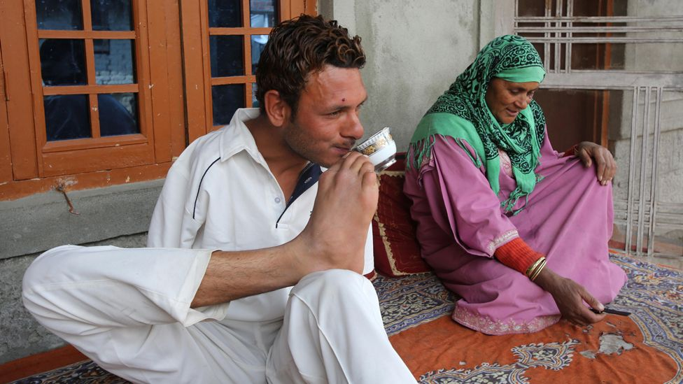 Amir drinks a cup of tea - he holds the cup in his foot