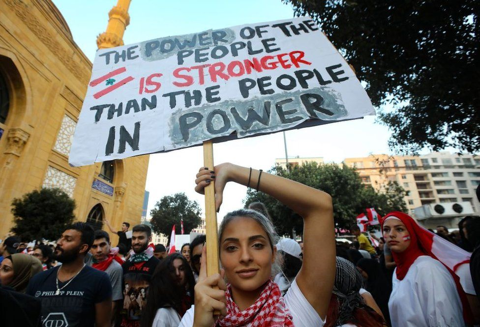 A woman holds a sign while protesting in Beirut