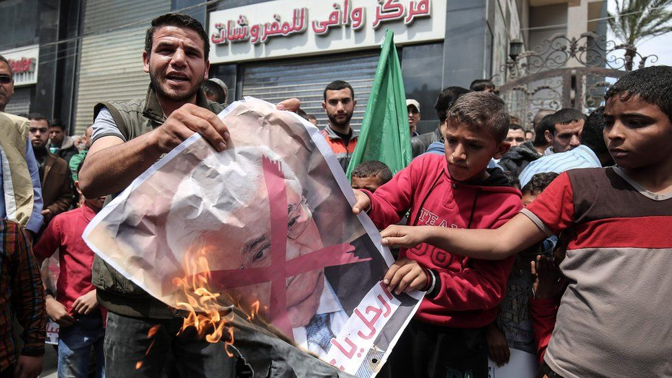 Hamas supporters burn a poster of Mahmoud Abbas at a protest against power cuts in Khan Younis, Gaza (14 April 2017)