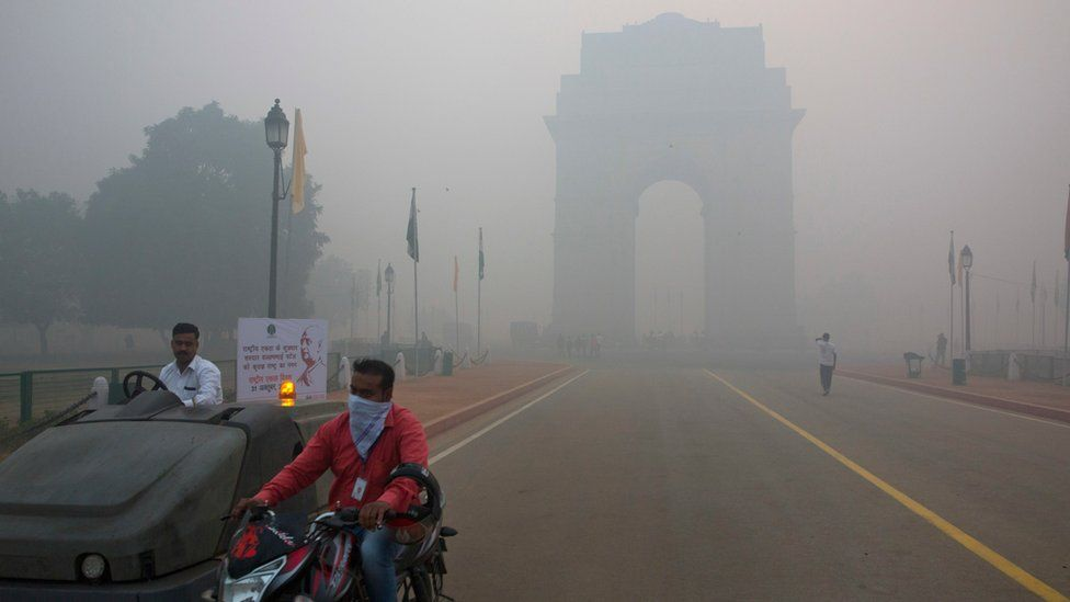 A man covers his face with a scarf as he rides in front of the landmark India Gate, enveloped by smoke and smog, on the morning following Diwali festival in New Delhi