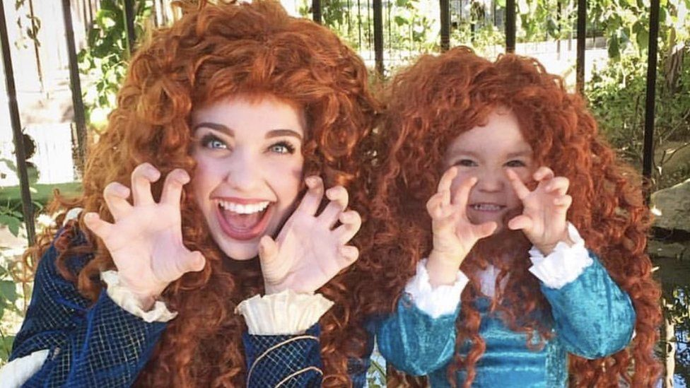 A mother and daughter dressed as matching Disney princesses