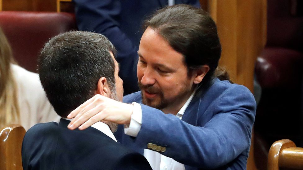 Podemos leader Pablo Iglesias (R) embraces Jordi Sànchez