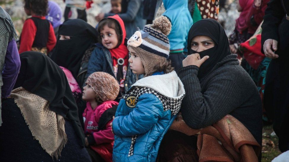 Displaced Syrians from Idlib province queue to receive food aid from a truck