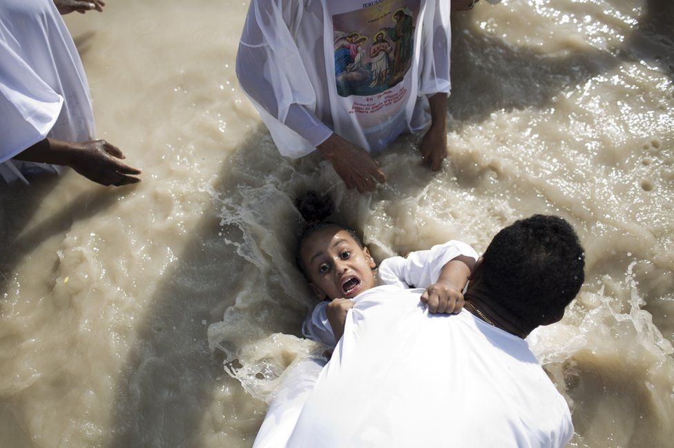 An Eritrean Orthodox Christian pilgrim is baptised at the Qasr El-Yahud baptism site on the west bank of the River Jordan.
